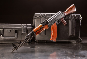 Studio shot of a Russian AK-47 in front of pelican cases, ready for travel.