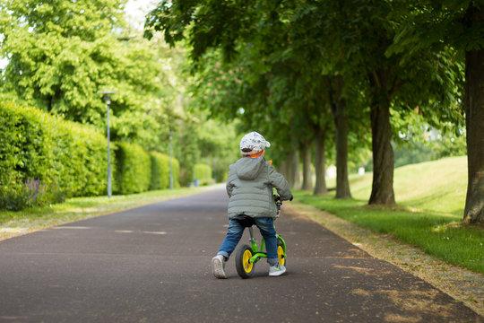 kleiner Junge auf seinem Laufrad