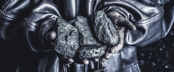 Coal mining :miner hold in the hand. Picture idea about coal mining or energy source, environment protection.  Volcanic rock.