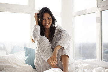 Asian Woman Sitting on Bed at Home