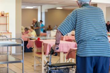 Personne agée avec déambulateur au restaurant de la maison de retraite