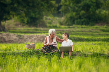Happy moments with grandmother and grandson are used laptop for learning sitting in the rice paddy countryside at Thailand.