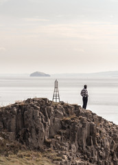 Obraz Girl on the top of a hill looking to a island with vintage clothes  - fototapety do salonu