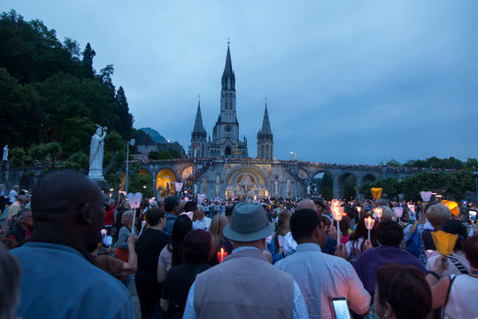 Lourdes, France, 24 June 2019: Evening procession with candles at the shrine of Lourdes