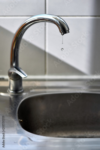 Clean water drops falling from a dripping kitchen faucet, an ...