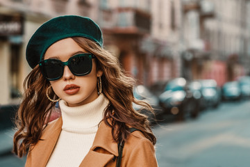 Outdoor autumn portrait of young elegant fashionable lady wearing trendy big sunglasses, green beret, hoop earrings, camel coat, white turtleneck,walking in street of European city. Copy, empty space