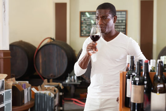 Confident african american male winemaker inspecting quality of red wine, checking it in wine store