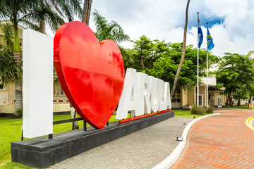 ORANJESTAD, ARUBA - JULY 25, 2017: I Love Aruba sign stands in front of the parliament building. Aruba, a constituent of the Kingdom of the Netherlands, is a parliamentary representative democracy.