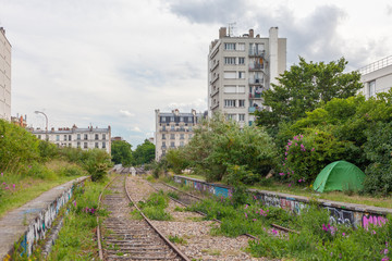 Olr railroad in an industrial area with some vegetation