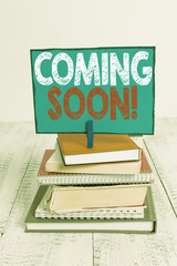 Writing note showing Coming Soon. Business concept for event or action that will happen after really short time pile stacked books notebook pin color reminder white wooden