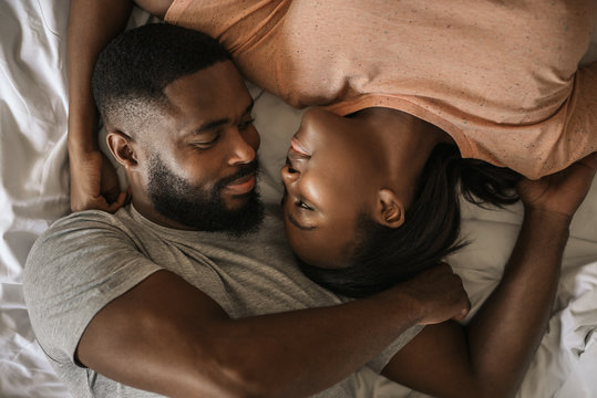 Loving African American couple looking at each other in bed