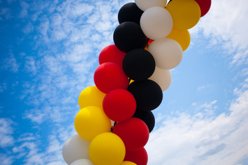 Balloons - Colors of the German National Flag (black, red, yellow)  - outdoors against blue Sky with white Clouds - Symbol for Festivity or Celebration
