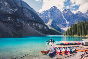 Colorful canoes in blue turquoise waters in Moraine Lake, Banff National Park, Alberta, Canada