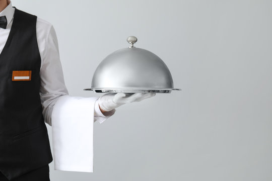 Handsome waiter with tray and cloche on light background