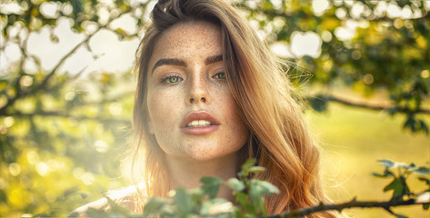 Sensual girl with freckles posing in sunny garden.