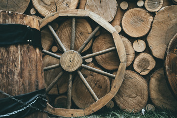 Wooden wheel on wood rustic background, vintage toned