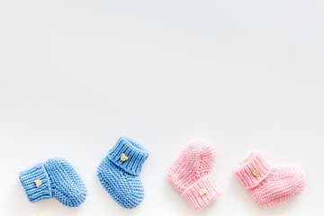 Cute baby booties for girl and boy on white background top view copyspace