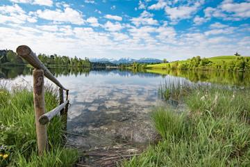 Alter verwitterter Holzsteg führt in einen klaren Bergsee
