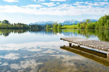 Holzsteg führt in einen Bergsee hinein