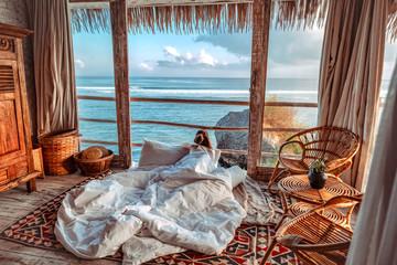Fototapeta Woman enjoying morning vacations on tropical beach bungalow looking ocean view Relaxing holiday at Uluwatu Bali ,Indonesia obraz