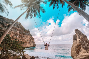 Beautiful girl on swing coconut palms on beach at Daimond  beach, Nusa Penida island Bali ,Indonesia