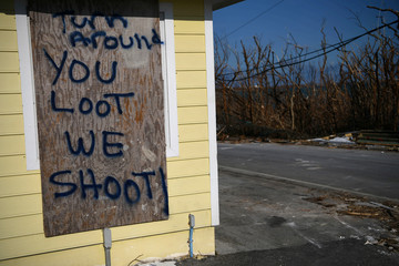 A sign warning against looting is seen at the entrance to a property in the wake of Hurricane Dorian in Marsh Harbour