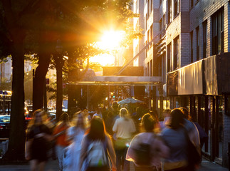 Fotomurales - Crowds of diverse people walking down the sidewalks of 14th Street with the bright light of summer sunset shining above in New York City