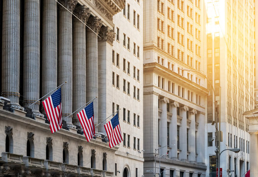 American flags flying in front of the historic buildings of Wall Street in the financial district of Manhattan, New York City