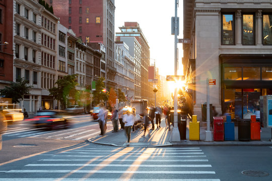 Man walking through the crosswalk at the busy intersection of 5th Avenue and 23rd Street in New York City with sunset background