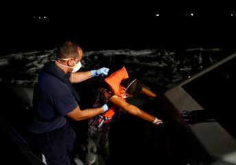 A Tunisian migrant is frisked by Armed Forces of Malta sailors during his medical evacuation in international waters off Malta in the central Mediterranean Sea