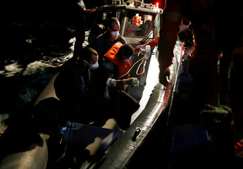 A Tunisian migrant is assisted by Armed Forces of Malta sailors during his medical evacuation in international waters off Malta in the central Mediterranean Sea