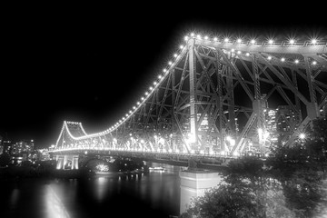 A monochrome photo of Story Bridge in Brisbane lighting up with a lot of beautiful lights at night time, Queensland, Australia.