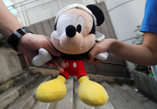 Secondary schools hold a stuffed doll of Mickey Mouse with its eye covered as they form a human during a protest against the police brutality, after clash with protesters at Wan Chai district in Hong Kong