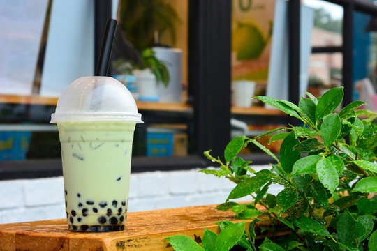glass of milk bubble matcha green tea with tapioca pearls on wooden table with green leaves on blurred cafe restaurant background
