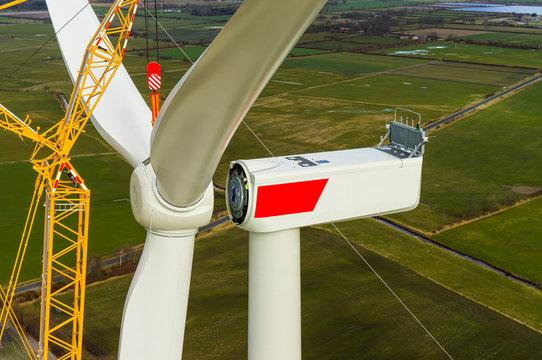 Windenergieanlage bei der Montage vom Stern mit Rotorblättern Luftbild und Nahaufnahme einer