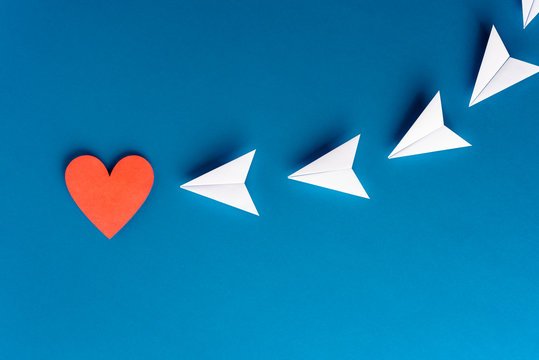 Focus, assertiveness, work yourself concept. Paper heart shape with airplane on blue background