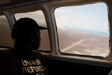 A woman looks down through an airplane window as the plane takes off during an evacuation operation after Hurricane Dorian hit the Abaco Islands in Marsh Harbour