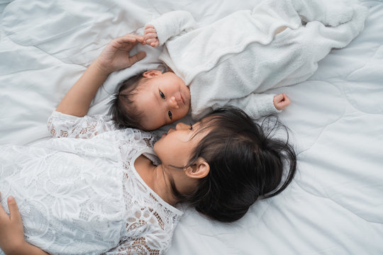 top view of infant baby and girl sibling enjoying together on bed