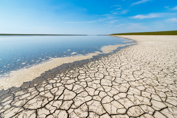 The coastline of the salt lake with blue sky, cracked dry ground and the green grassy line at the horizon. Gruzskoe lake, Rostov-on-Don region, Russia