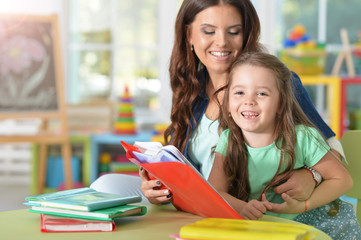 Portrait of mother and daughter reading books