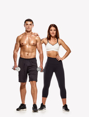 Portrait of strong healthy man and woman posing with dumbbells