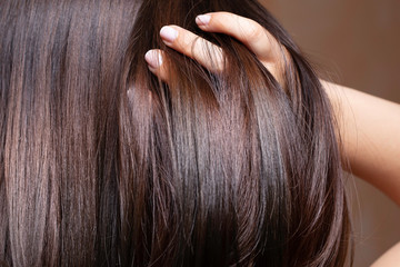 Fotobehang Kapsalon A beautiful brunette woman is seen closeup, stroking fingers through straightened and conditioned glossy brown hair with room for copy.