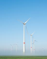 wind turbines in green meadow near aurich in ostfriesland on misty morning in august