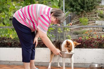 Geistig behinderte Frau füttert ihren Hund, tiergestützte und palliative Therapie