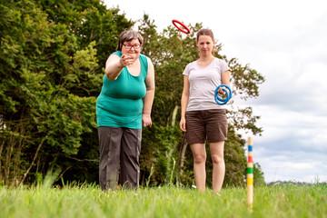 Geistig behinderte Frau und Betreuerin spielen zusammen Ringe werfen, Freizeit und Spiel