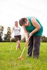 Geistig behinderte Frau beim Krocket spielen, Therapeutin im Hintergrund, palliative Therapie