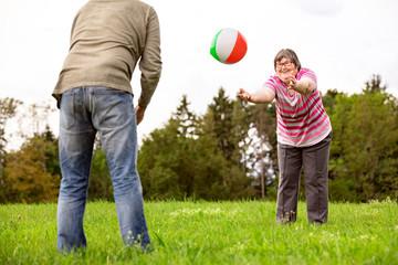 Geistig behinderte Frau spielt mit einem Ball, Geschicklichkeit und Konzentration durch Spiele