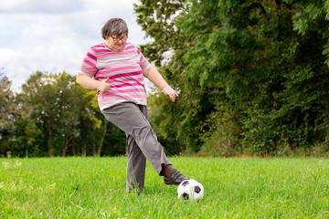 Geistig behinderte Frau spielt Fussball auf der Wiese, Geschicklichkeit und Training