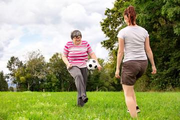 Geistig behinderte Frau spielt Fussball mit einer Pflegerin spielen gemeinsam Ball