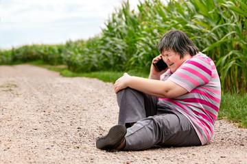 Verletzte geistig behinderte Frau ruft mit dem Smartphone Hilfe, selbstbestimmtes Handeln